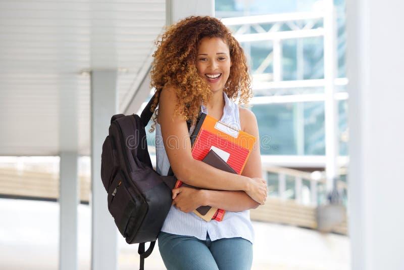 Glückliche Studentin, die auf dem Campus mit Büchern und Tasche lacht stockbilder