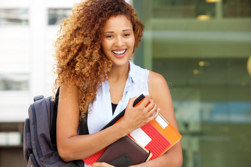 Glückliche Studentin, die auf dem Campus mit Tasche und Büchern lächelt stockfotos