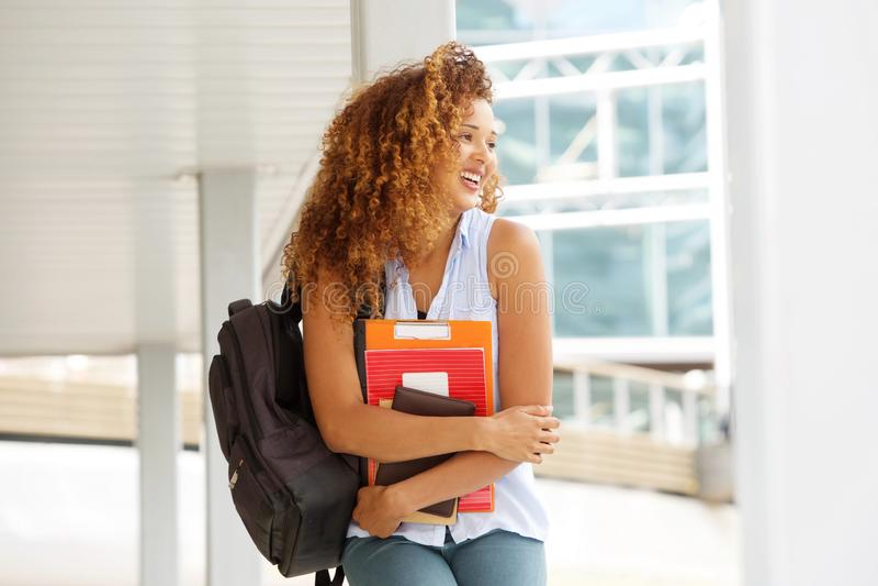 Glückliche Studentin, die draußen mit Büchern lacht lizenzfreie stockfotos