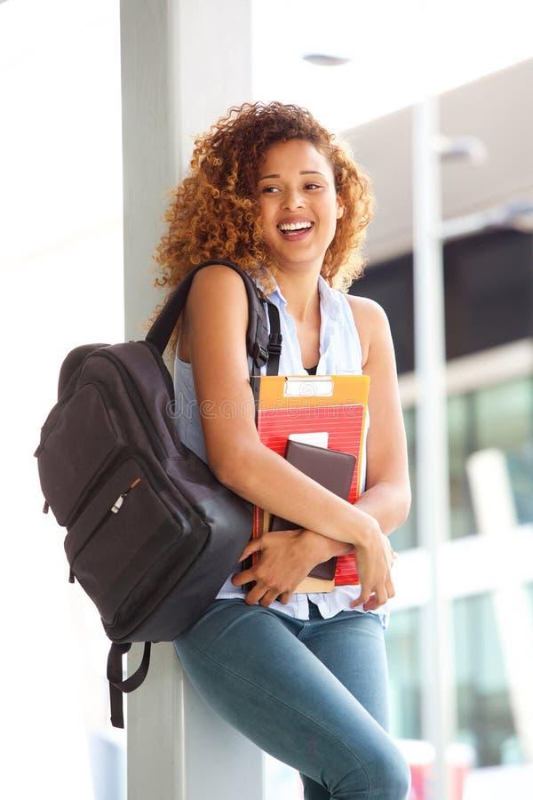 Glückliche Studentin, die draußen mit Tasche und Büchern lächelt lizenzfreie stockfotos