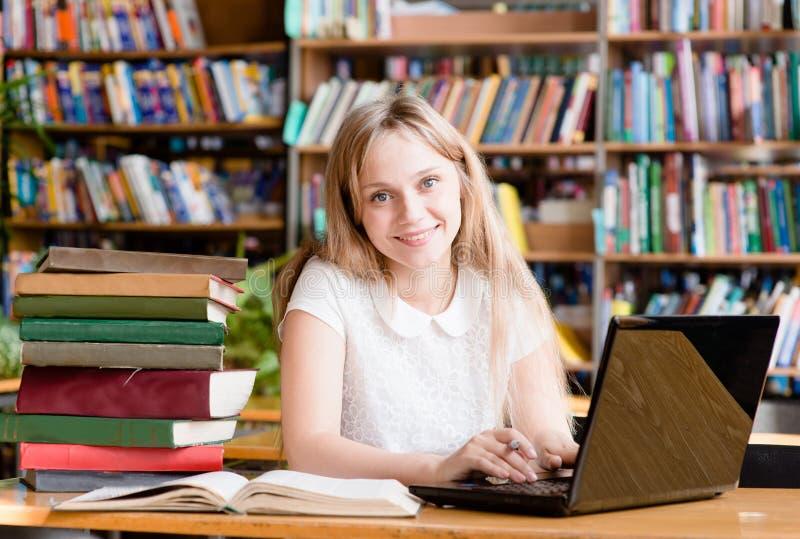 Glückliche Studentin-With Laptop In-Bibliothek lizenzfreie stockfotografie