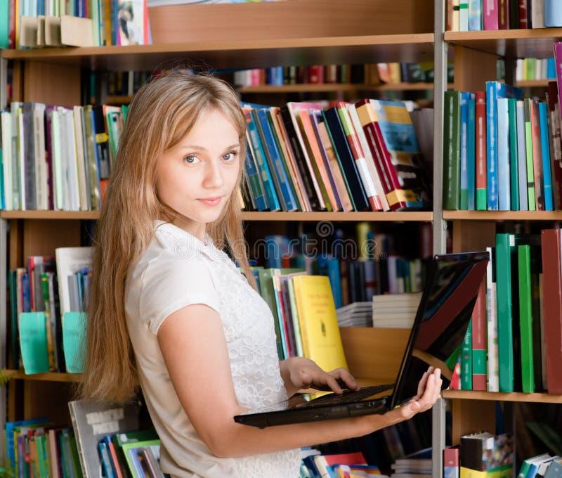 Glückliche Studentin-With Laptop In-Bibliothek stockfotografie