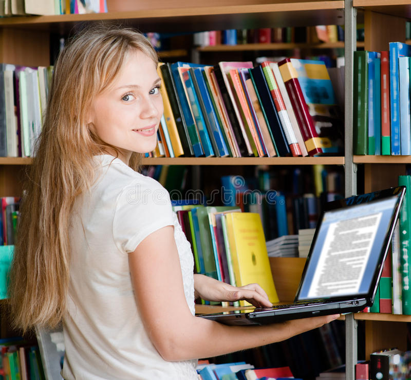 Glückliche Studentin-With Laptop In-Bibliothek stockbild