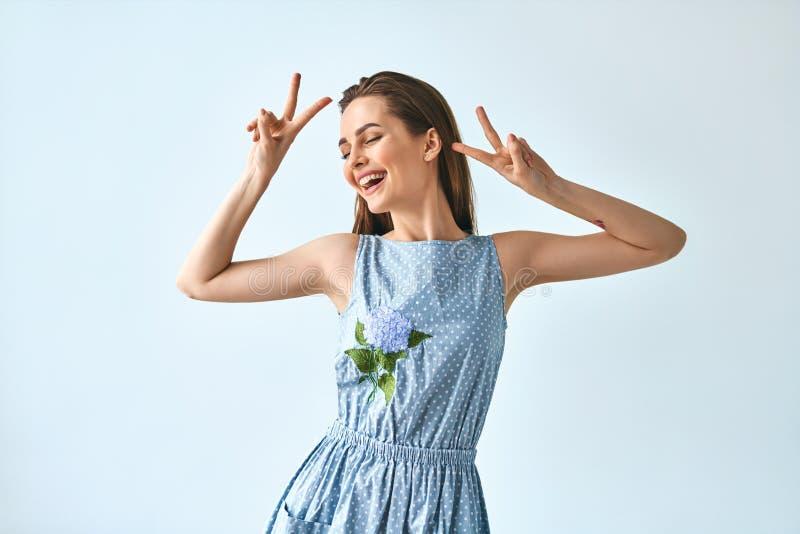 Glückliche tanzende Frau, die Friedenszeichen mit beiden Händen zeigt stockfoto