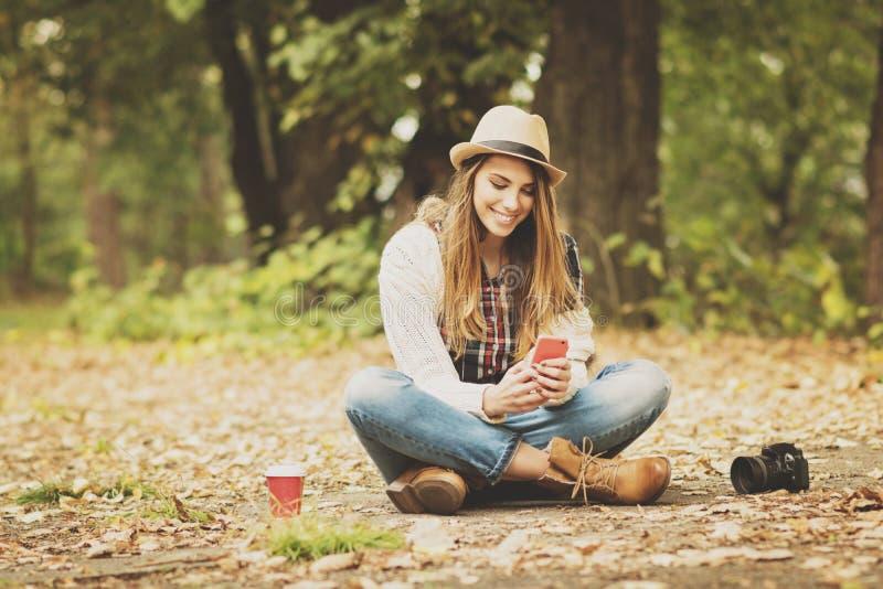 Glückliche tausendjährige junge Frau im Park im Herbst unter Verwendung des Smartphone lizenzfreies stockbild