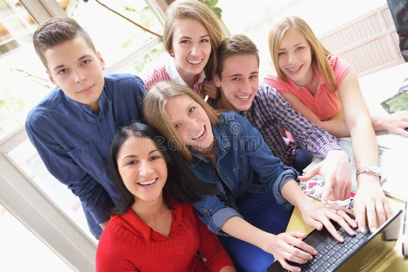 Glückliche Teenagergruppe in der Schule lizenzfreie stockbilder
