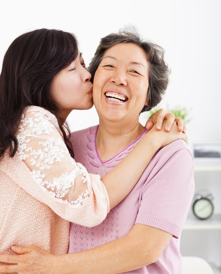 Glückliche Tochter, die ihre Mutter küsst stockbild