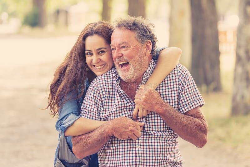 Glückliche Tochter, die ihren älteren Vater von der Rückseite im Park umfasst stockfotos