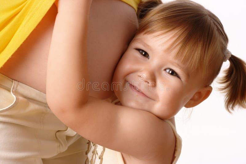 Glückliche Tochter umfassen ihre schwangere Mutter stockfotografie