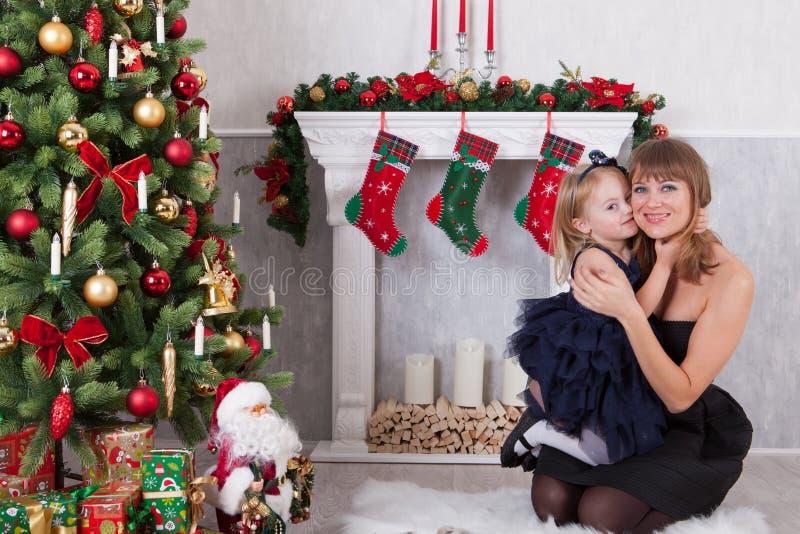Glückliche Tochter umfasst die Mutter, die nahe einem weißen Kamin nahe bei einem Weihnachtsbaum stationiert stockfotografie