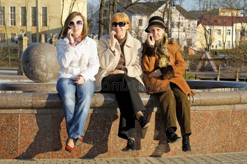 Glückliche Tochtermamma und -oma sprechen durch beweglichen Verkauf stockbild