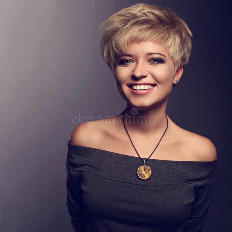 Glückliche toothy lachende Frau mit kurzer blonder Pendelfrisur in GR lizenzfreie stockbilder