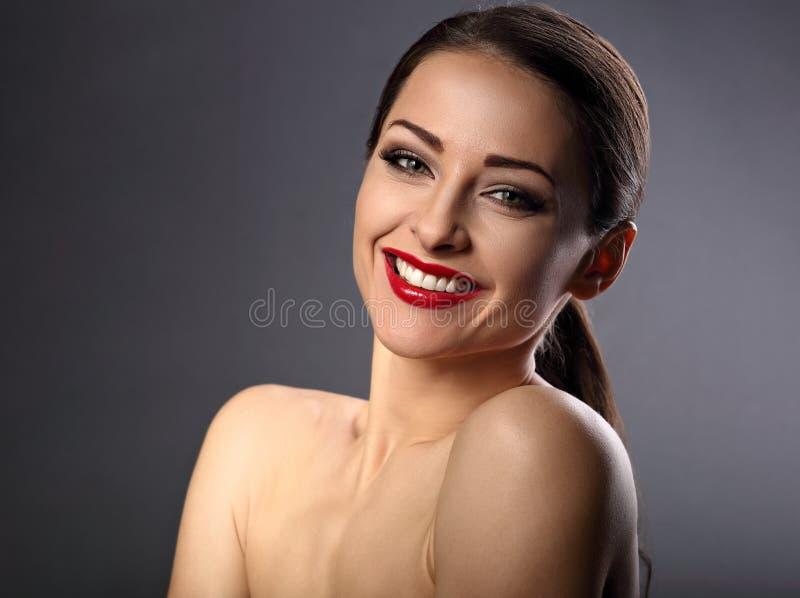 Glückliche toothy lachende Schönheitsfrau mit dem roten Lippenstift, der an schaut lizenzfreies stockbild