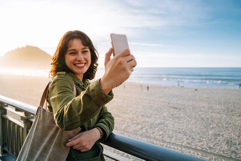 Glückliche touristische Frau, die selfie mit ihrem intelligenten Telefon nimmt lizenzfreie stockfotografie