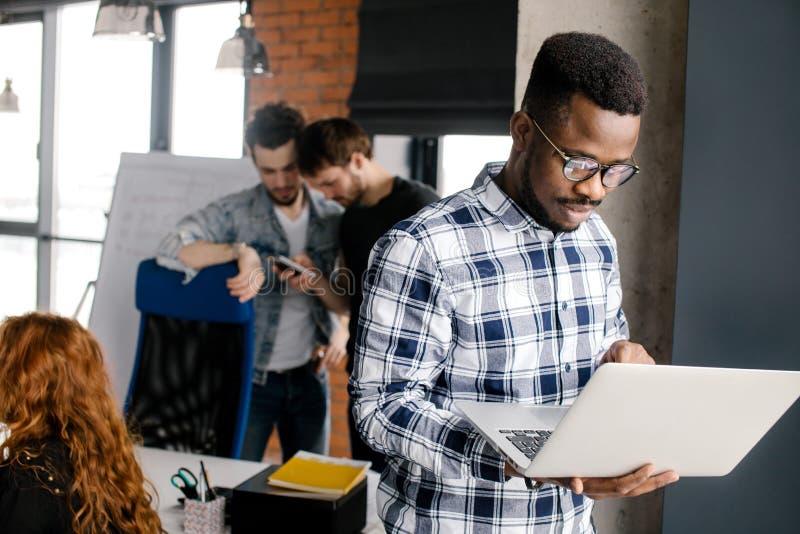 Glückliche tragende Glasfunktion des jungen Mannes auf seinem Laptop stockbild
