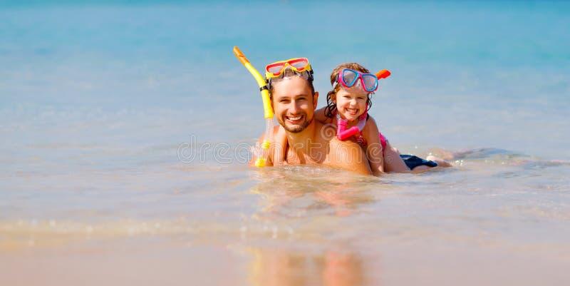 Glückliche tragende Maske des Familienvaters und -kindes und Lachen auf beac lizenzfreie stockfotografie