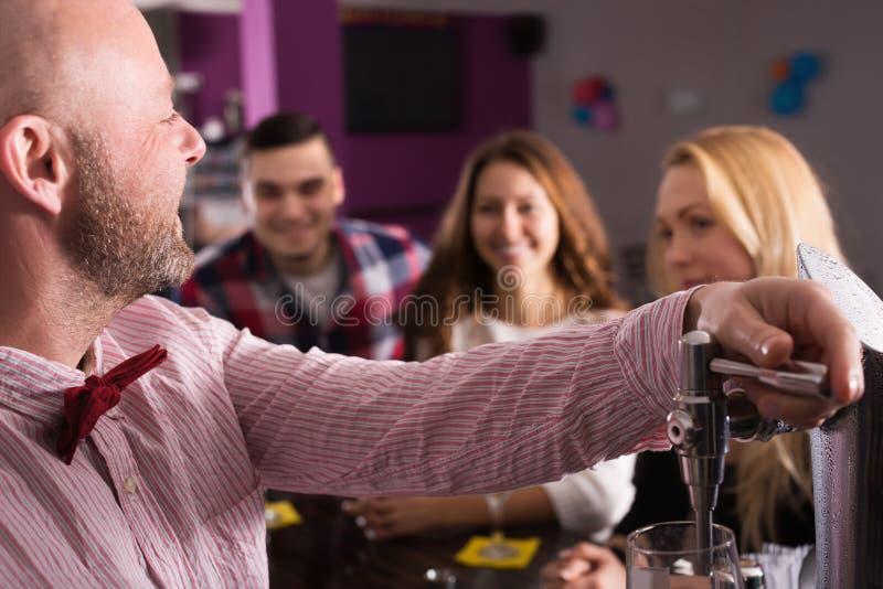 Glückliche trinkende und plaudernde Freunde stockbild