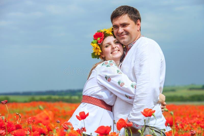 Glückliche ukrainische Paare auf dem Blütenmohnblumengebiet stockbilder
