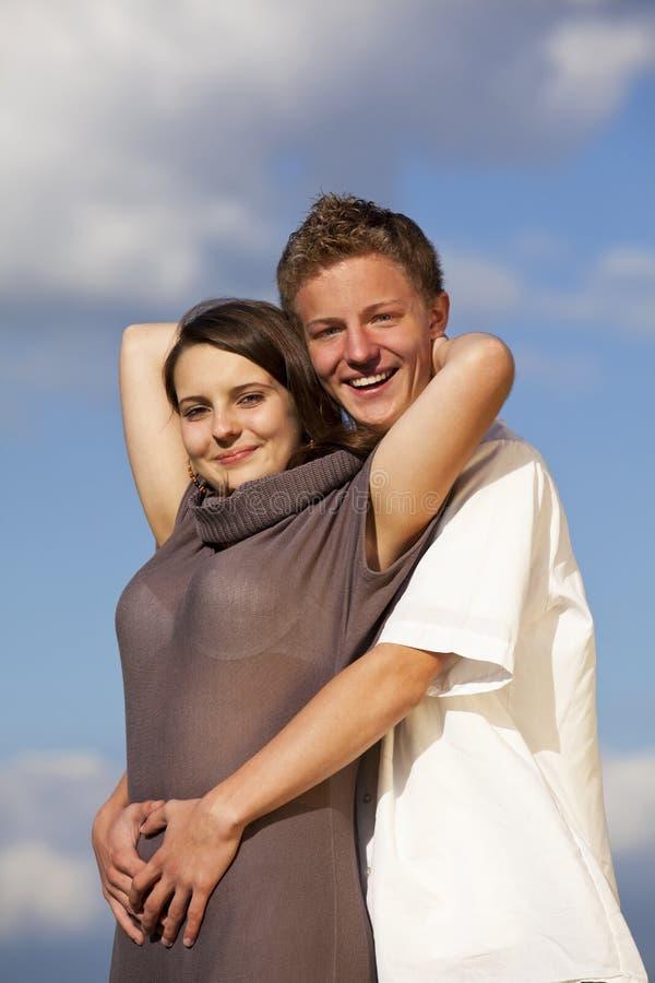 Glückliche umarmende Jugendpaare stockbild