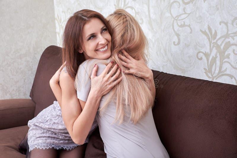 Glückliche Umarmung jede eine andere und auf Sofa im Wohnzimmer sitzen der Frau zwei zu Hause stockbilder