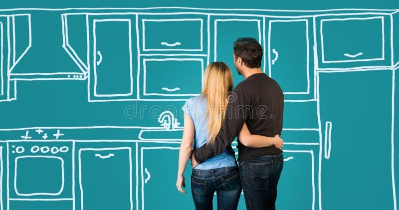Glückliche Umfassungspaare, die ihre Hauptküche versorgt bezüglich planen stockbilder