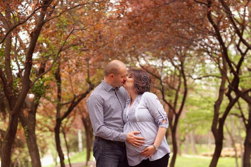 Glückliche und der Junge schwangere Paare, die in der Natur umfassen stockfotos
