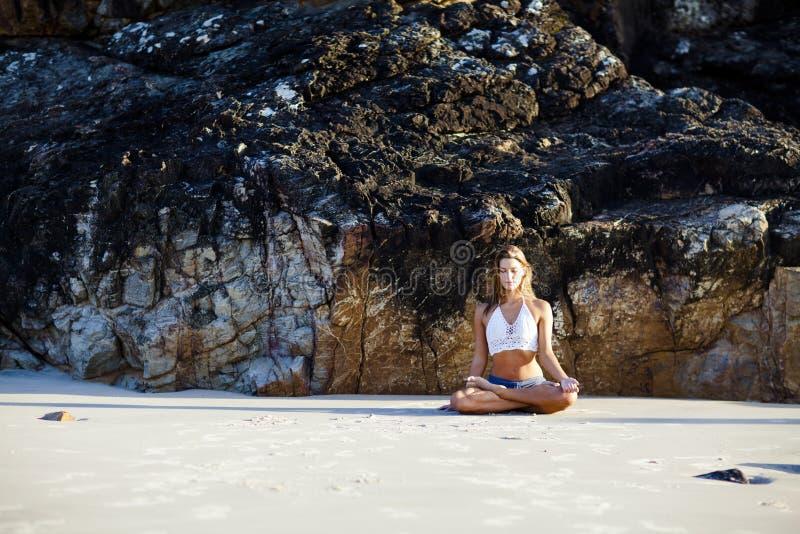 Glückliche und gesunde Frau, die auf Strand meditiert lizenzfreies stockfoto