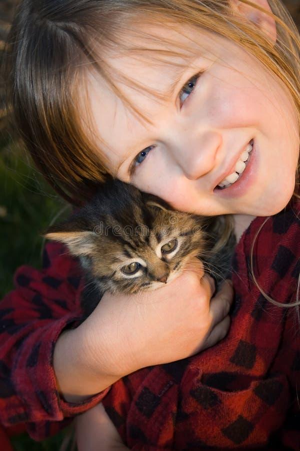 Glückliche und hübsche Kindholding ihr Kätzchen. stockbilder