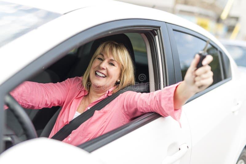 Glückliche und lächelnde ältere Frau im schwarzen Auto lizenzfreies stockfoto