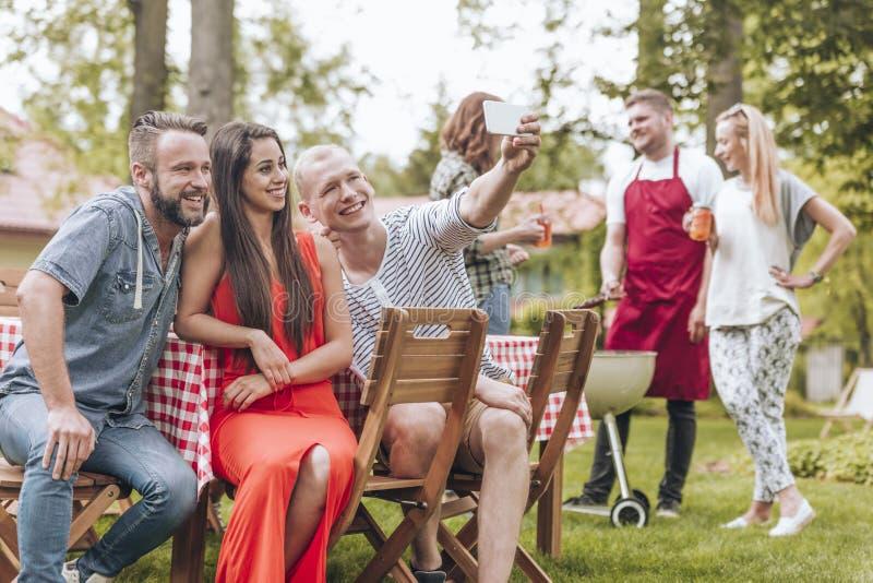 Glückliche und lächelnde Freunde, die Foto während der Grillpartei im Sommer machen lizenzfreie stockfotografie