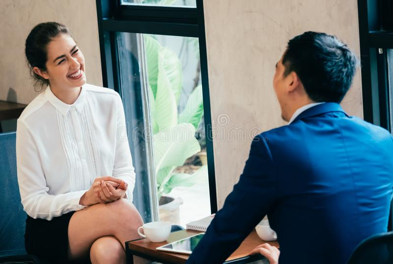 Glückliche und lächelnde Geschäftsberufstätige frau in der Diskussion mit anderem männlichem Geschäftsmannpartner im Team im Konf stockbild