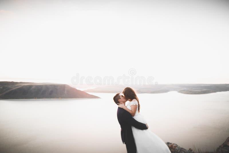 Glückliche und romantische Szene gerade von den verheirateten jungen Hochzeitspaaren, die auf schönem Strand aufwerfen lizenzfreie stockbilder