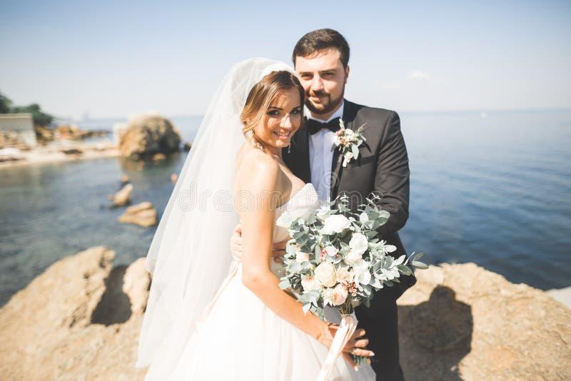 Glückliche und romantische Szene gerade von den verheirateten jungen Hochzeitspaaren, die auf schönem Strand aufwerfen lizenzfreies stockfoto