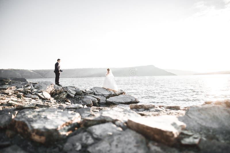 Glückliche und romantische Szene gerade von den verheirateten jungen Hochzeitspaaren, die auf schönem Strand aufwerfen stockfotos