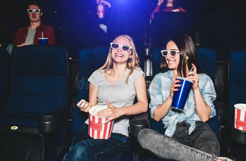 Glückliche und schöne Mädchen sitzen in der Kinohalle und in aufpassendem Film Blondes Mädchen schaut gerade und Lächeln stockfotografie