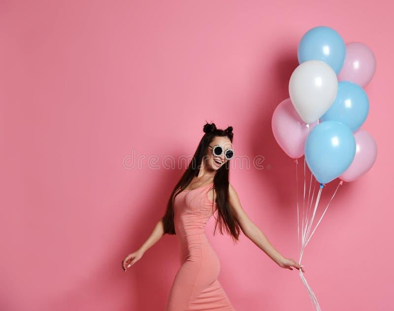 Glückliche und sexy Frau, die mit Rosa und blauen Ballonen auf rosa Hintergrund, Atelieraufnahme aufwirft stockfotos