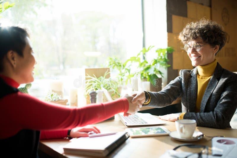 Glückliche Unternehmer, die Händedruck im Café machen lizenzfreie stockfotos