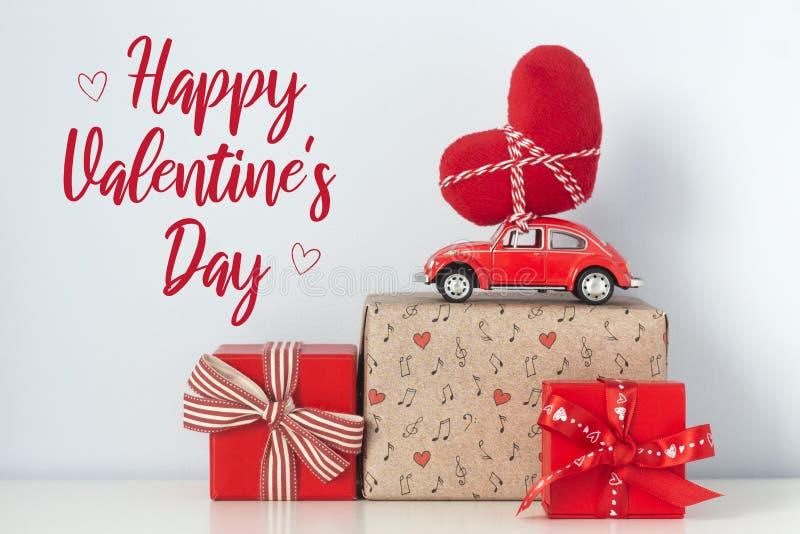 Glückliche Valentinsgruß `s Tageskarte Rotes Retro- Spielzeugauto mit Plüschherzen lizenzfreie stockfotografie