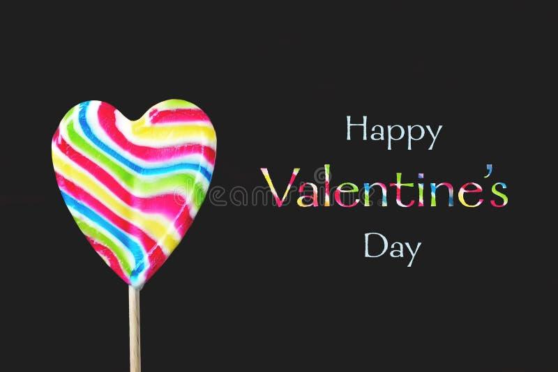 Glückliche Valentinsgrußtageskarte Herz formte den Lutscher, der auf schwarzem Hintergrund lokalisiert wurde lizenzfreies stockbild