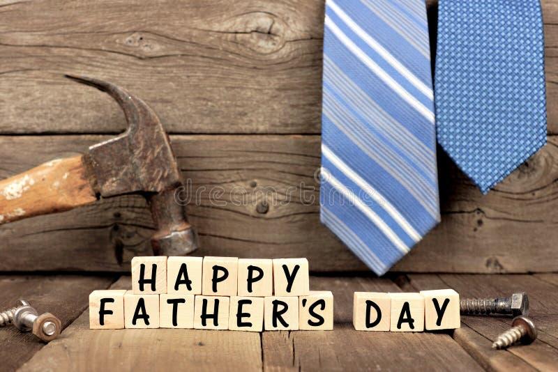 Glückliche Vatertagsblöcke mit Werkzeugen und Bindungen gegen Holz lizenzfreies stockbild