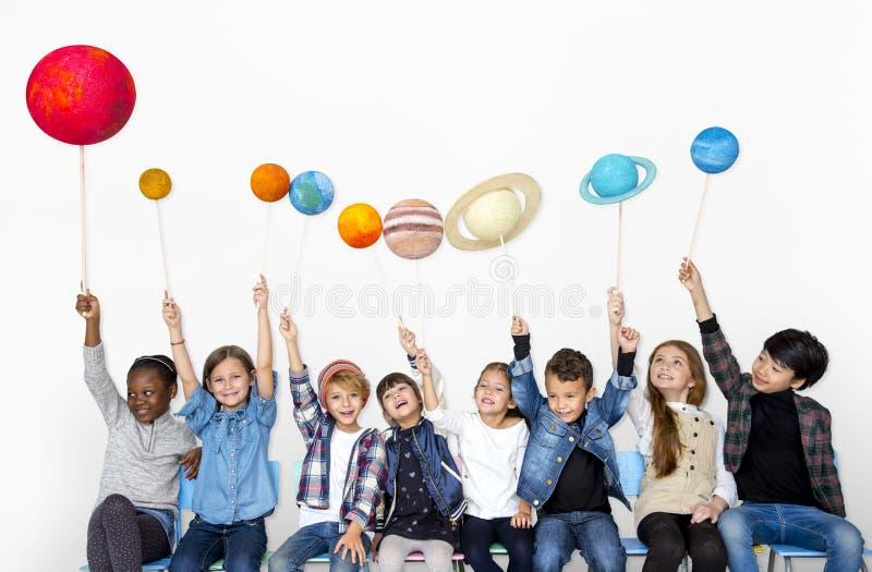Glückliche verschiedene Gruppe Kinder, die Planeten halten stockbilder