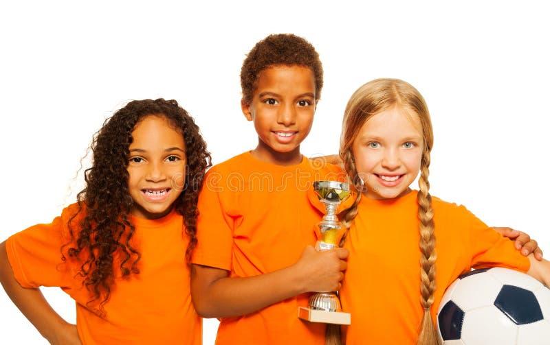 Glückliche verschiedene Kindersieger von Fußballspielen lizenzfreies stockfoto