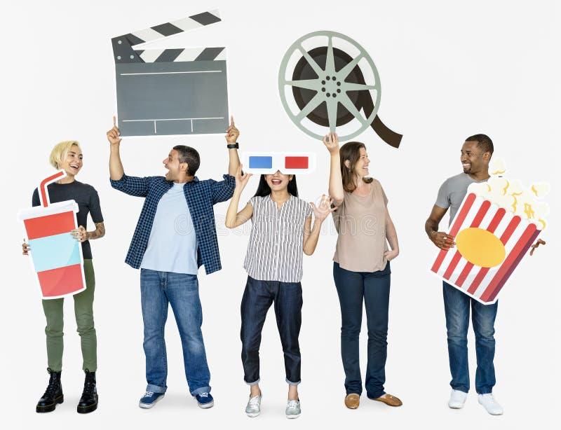 Glückliche verschiedene Leute, die Filmikonen halten stockfotografie