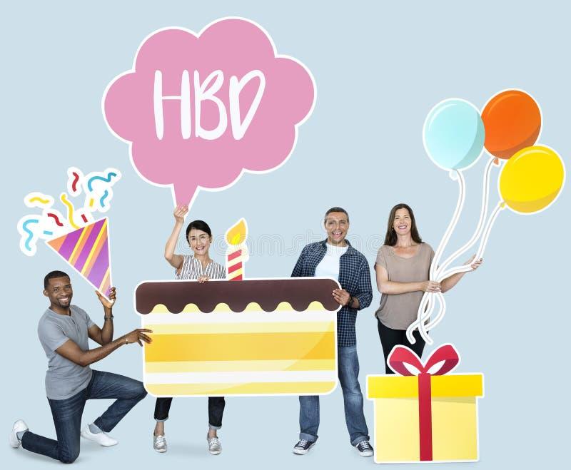 Glückliche verschiedene Leute, die Geburtstagskuchen halten lizenzfreies stockbild