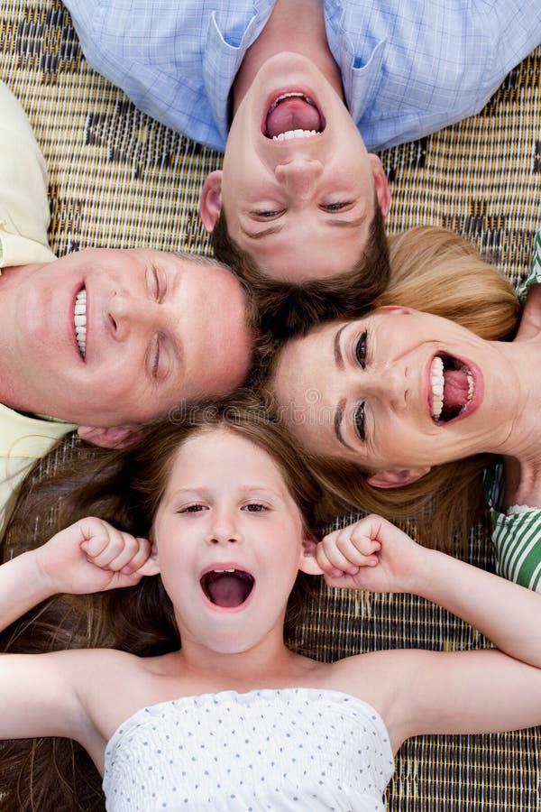 Glückliche vierköpfige Familie, die auf dem Teppich liegt lizenzfreie stockfotos