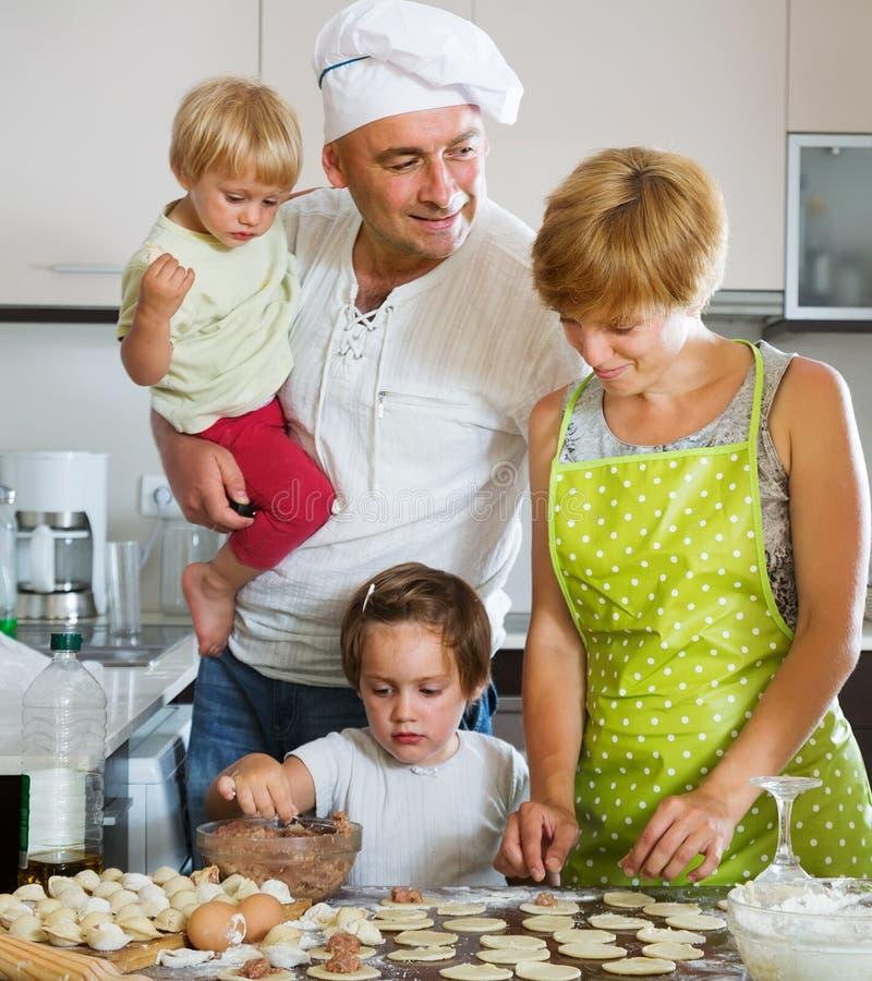 Glückliche vierköpfige Familie, die Fleischmehlklöße (pelmeni, macht) lizenzfreie stockfotos