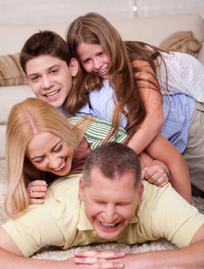 Glückliche vierköpfige Familie, die Spaß im Bett hat stockfotografie
