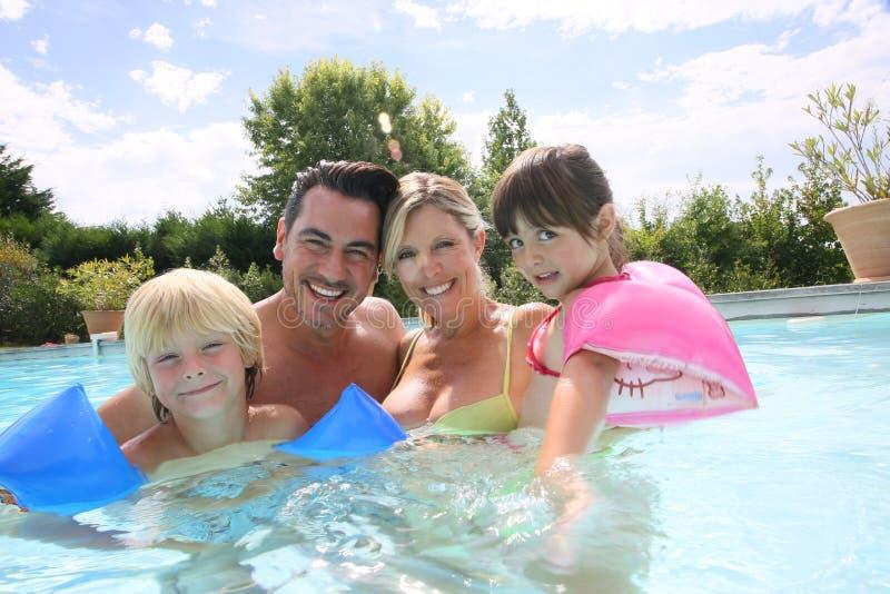 Glückliche vierköpfige Familie, die Swimmingpool genießt stockbild