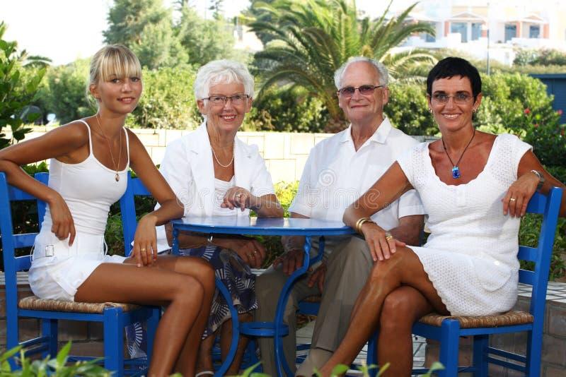 Glückliche vierköpfige Familie im Garten lizenzfreie stockbilder