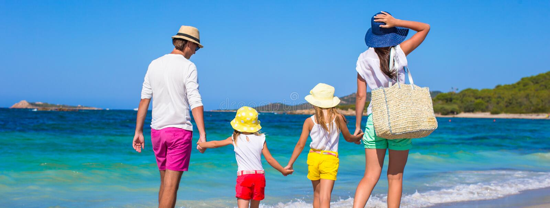 Glückliche vierköpfige Familie während der Strandferien lizenzfreie stockfotos
